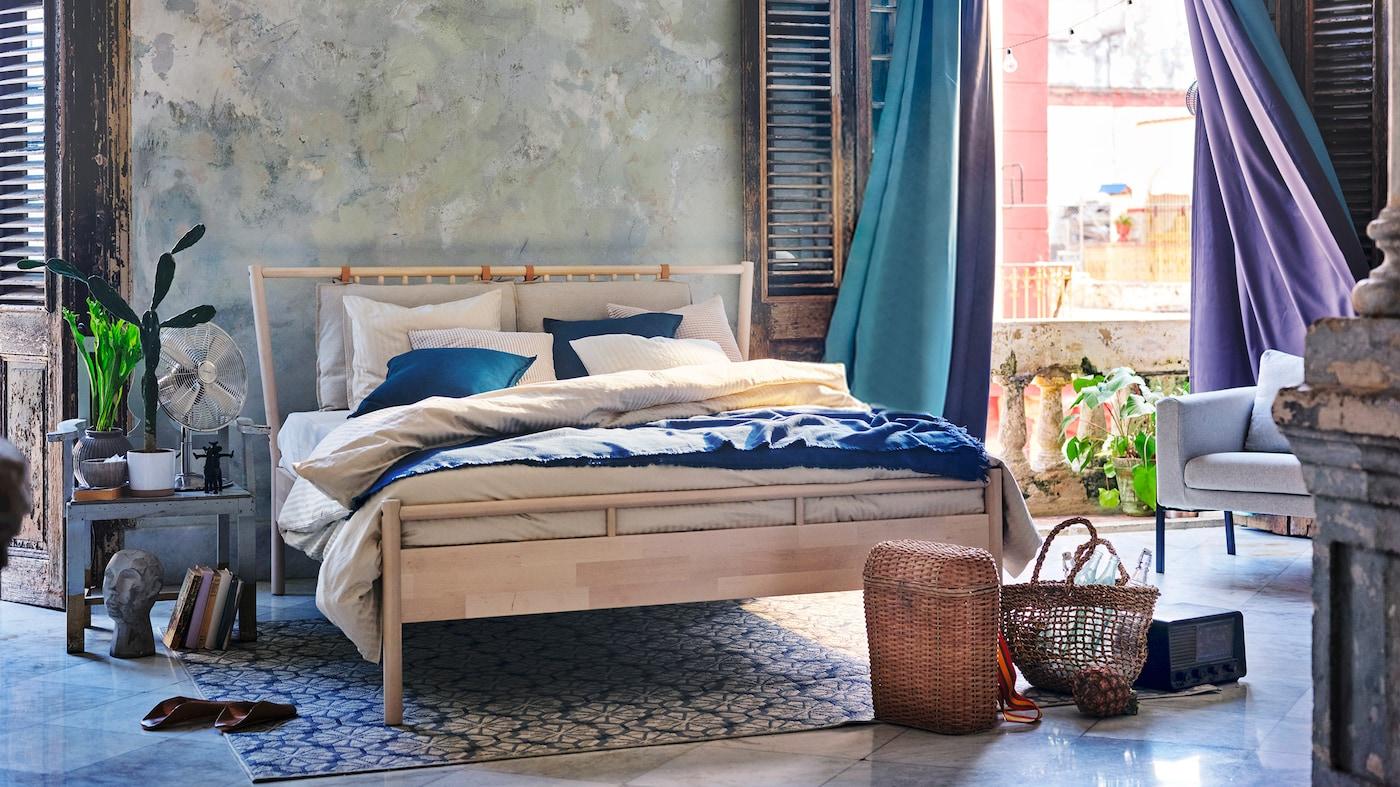En dobbeltseng af træ med hvidt og blåt sengetøj i et soveværelse med store åbner vinduer med skodder og blå og lilla gardiner.