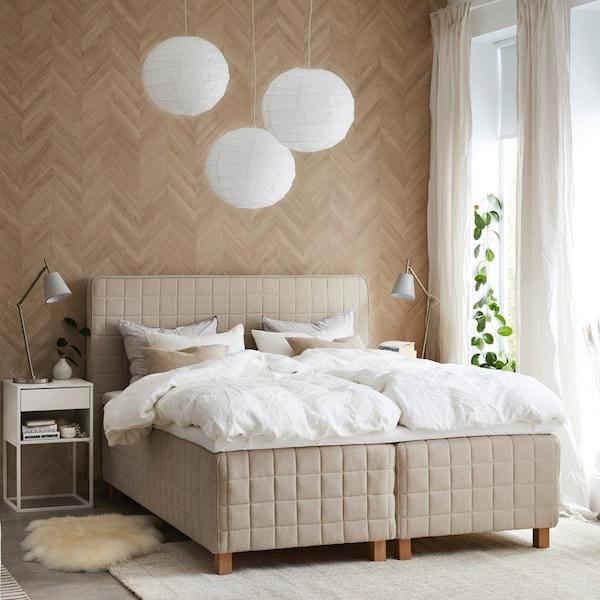 En dobbeltseng bestående af to boxmadrasser med sengegavl står i et soveværelse.
