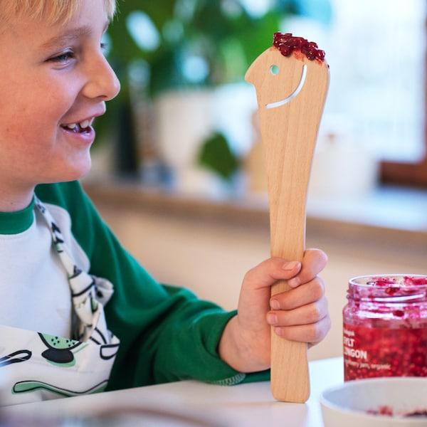 En dreng holder en UPPLIVAD træske med SYLT LINGON tyttebærsyltetøj på et køkkenbord – skeen har et udskåret smilende ansigt.