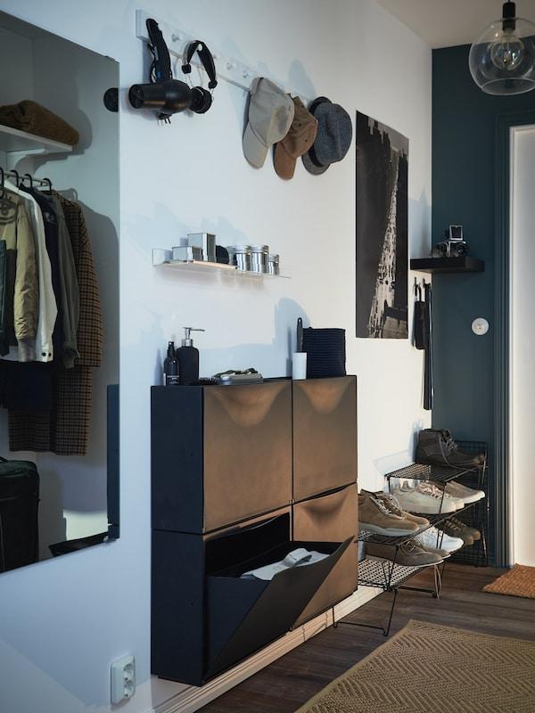 En entre med hvide vægge og sorte skoskabe.