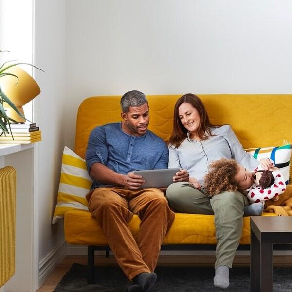 En familie sidder på en gul sofa og orienterer sig på en tablet