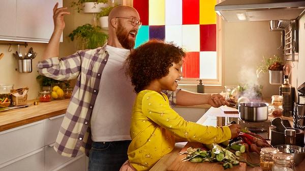 En far med sin datter i et køkken. De laver mad sammen. Hun har en gul trøje på. Bag den er en rude i forskelligfarvet tern