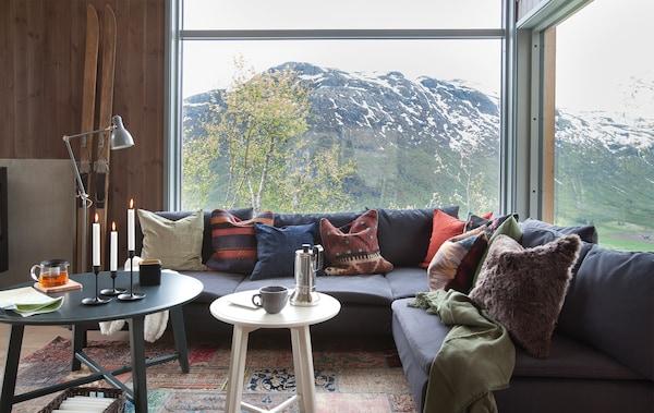 En fjellstue med stor sofa og puter i høstfarger med utsikt mot fjell ut vinduene.