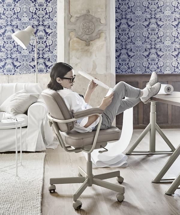 En flicka lutar sig tillbaka i en beige arbetsstol, med fötterna på ett skrivbord, på ett kontor med blåmönstrade tapeter.