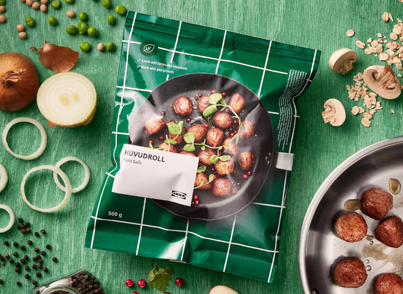 En förpackning med IKEA HUVUDROLL växtbaserade bullar på en grön träyta. Runt förpackningen ligger olika ingredienser.