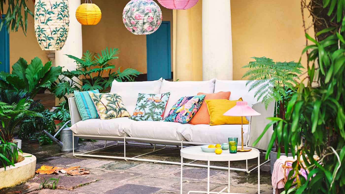 En gårdhave med fliser, hvor der står en beige, udendørs sofa med farverige puder med forskellige mønstre med bl.a. palmer. Der er også grønne planter i gårdhaven og LED-rispapirlamper med samme mønstre som puderne.
