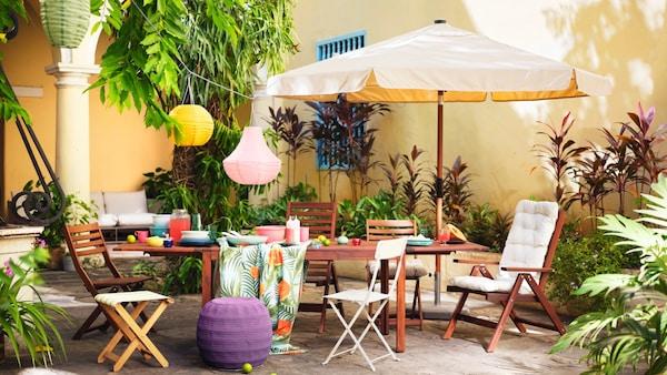 En gårdhave med havebord og havestole i mørk træ og masser af farverige detajler