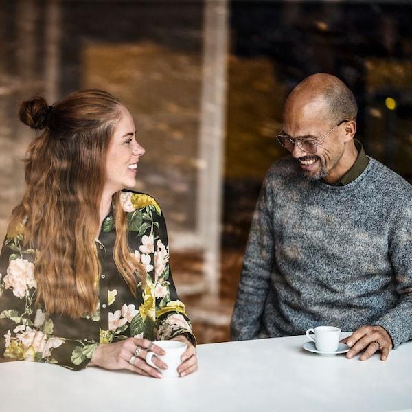 En glad man och en leende kvinna dricker kaffe tillsammans.