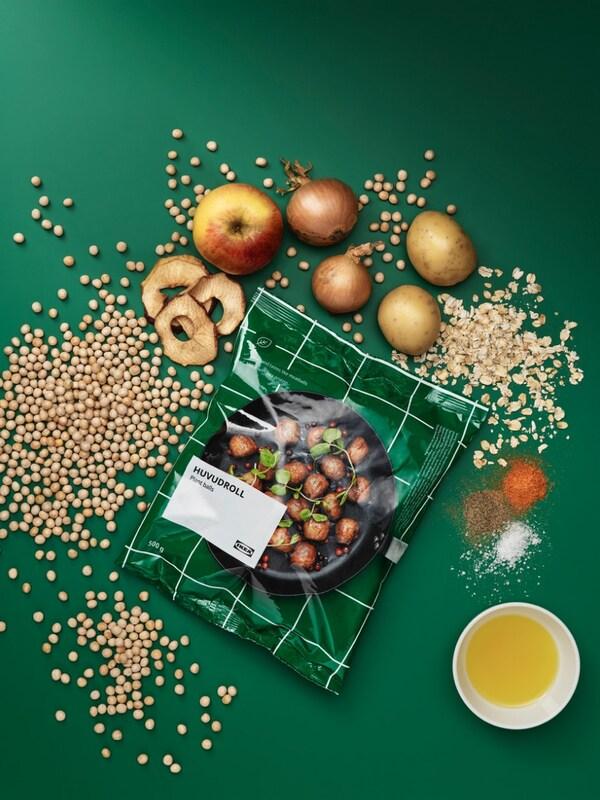 En grøn baggrund med en pose med plantebaserede boller, omringet af alle dens ingredienser, æble, løg, krydderier, ærter, kartofler.