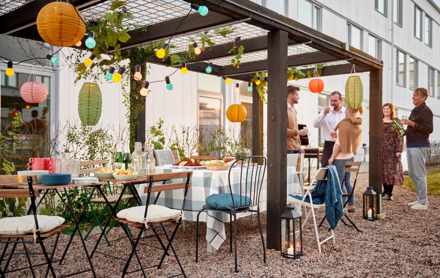 En gruppe mennesker står ved en række stole og små borde, der er dækket op til fest under en pyntet pergola i en gårdhave.