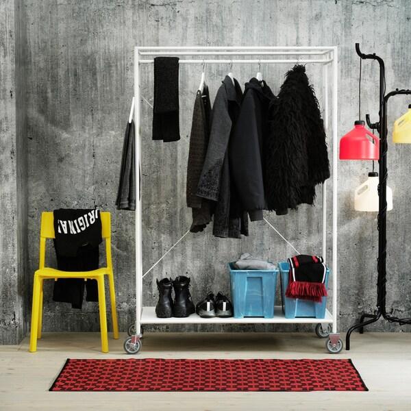 En gul stol ved siden af et hvidt tøjstativ og en stander lampe i sort med skræme i rød, gul og hvid. I baggrunden en rå betonvæg og i forgrunden et rødt mønstret tæppe