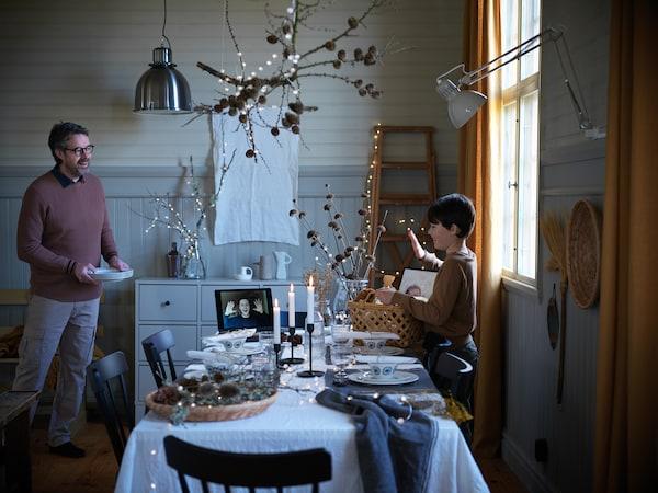 En gutt vinker til en person på en videosamtale på en festkledd spiseplass med levende lys – gutten har en kurv full av gaver.