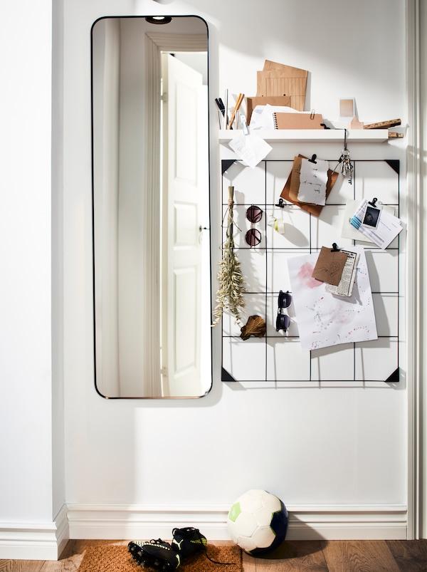 En hall med en lång spegel, en hylla och en svart SÖSDALA anslagstavla i stål med klips med olika lappar.