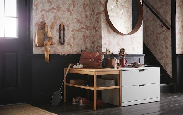 En hall med en ljusgrå NORDLI byrå med två lådor under en rund spegel och bredvid en träbänk med öppna hyllor.