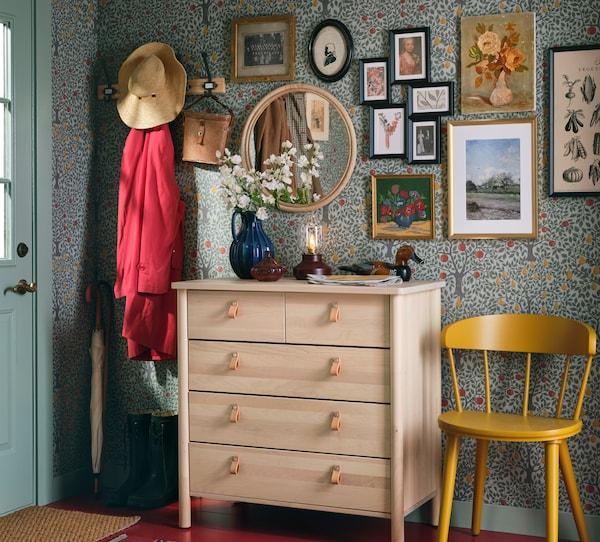 En hall med krokar för att hänga kläder, en gul stol och en BJÖRKSNÄS byrå med fem lådor av massiv björk.