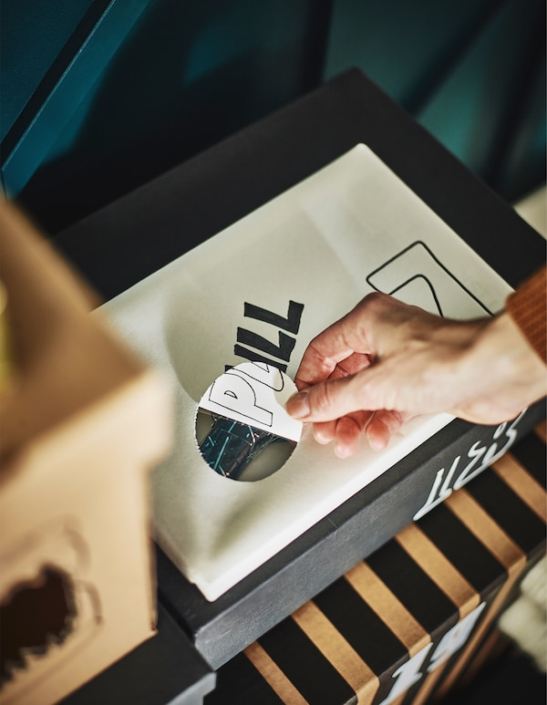 En hand lyfter på en pappersflik som täcker ett hål i en låda där man kan skymta ett inslaget paket.