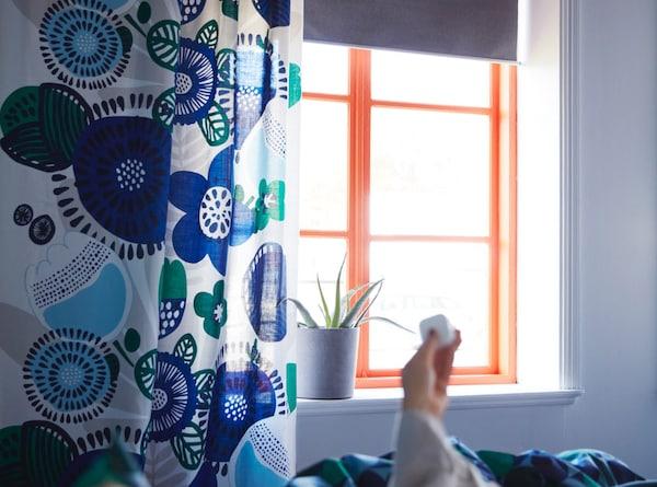 En hånd med fjernbetjening styrer elektriske gardiner