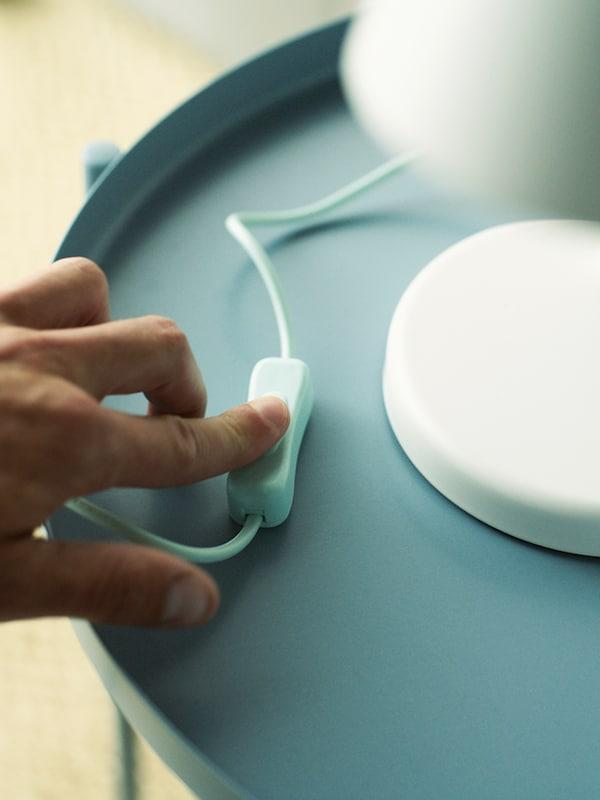 En hand som trycker på strömbrytaren på en vit bordslampa på ett ljusblått bord.