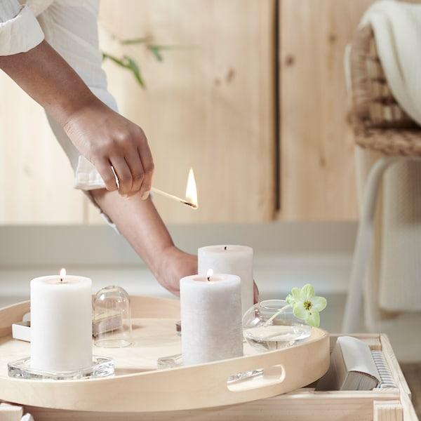 En hand tänder tre LUGGA doftande blockljus som står på en träbricka framför ett IVAR skåp i massiv furu.