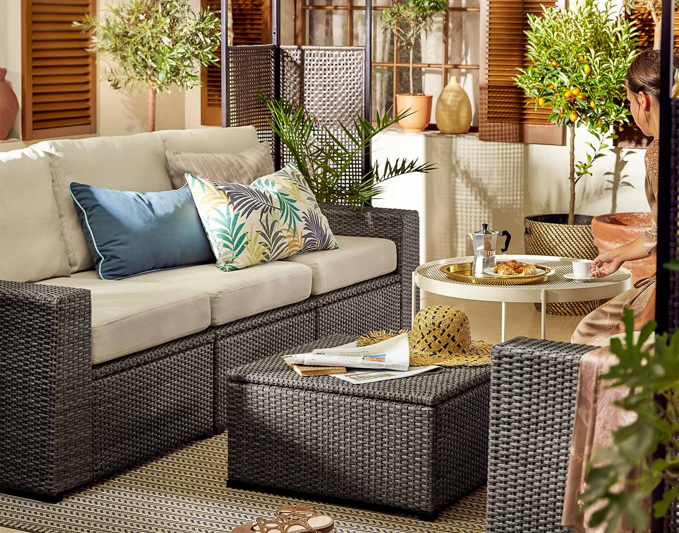 En havesofe med tilhørende lænestol og bord der står på en terrasse.