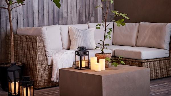 En hjørnesofa til brug udendørs fra SOLLERÖN serien står i aftenskumringen på en træterrasse. Der er også LED-lys, en grøn plante på bordet og hvide hynder i sofaen.