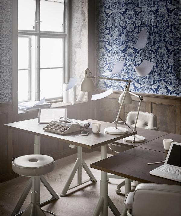 En höj- och sänkbart skrivbord och arbetsstol bredvid ett fönster i ett kontor med blåmönstrade tapeter.