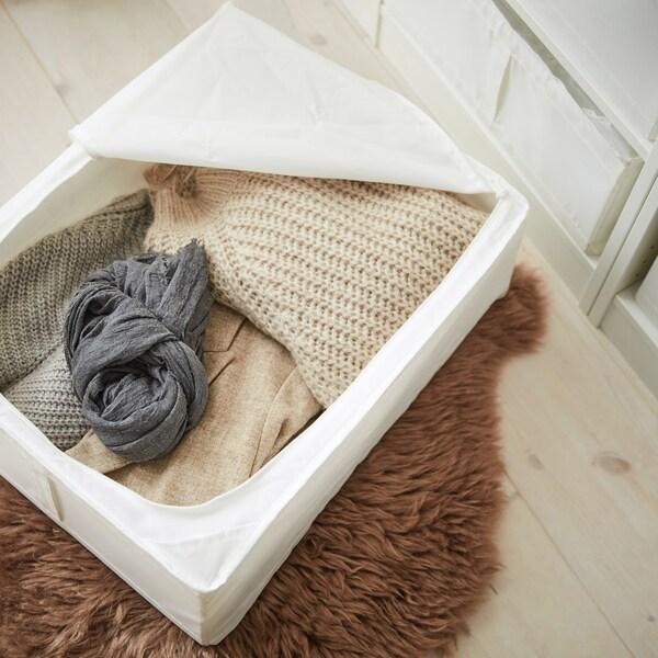En hvid boks med lynlås, hvor der er åbent og et kig ned til tøjet, der ligger beskyttet i kassen.