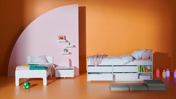 En hvid børneseng og en højere børneseng fra SLÄKT serien med opbevaring nedenunder.