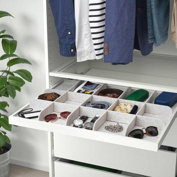 En hvid udtræksbakke med grå opdeler. I de små rum ligger der solbriller, ure, brilleetuier mv.