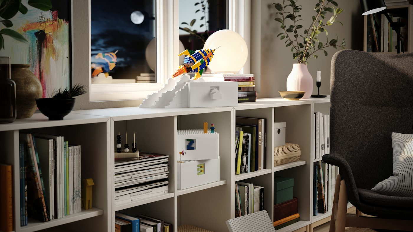 En hvit BYGGLEK boks står sammen med en rakett av LEGO-klosser på ei KALLAX hylle.