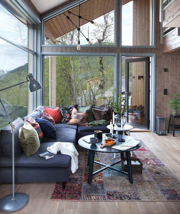 En hyttestue i fjellsiden med stor grå sofa og tekstiler i varme fargetoner.