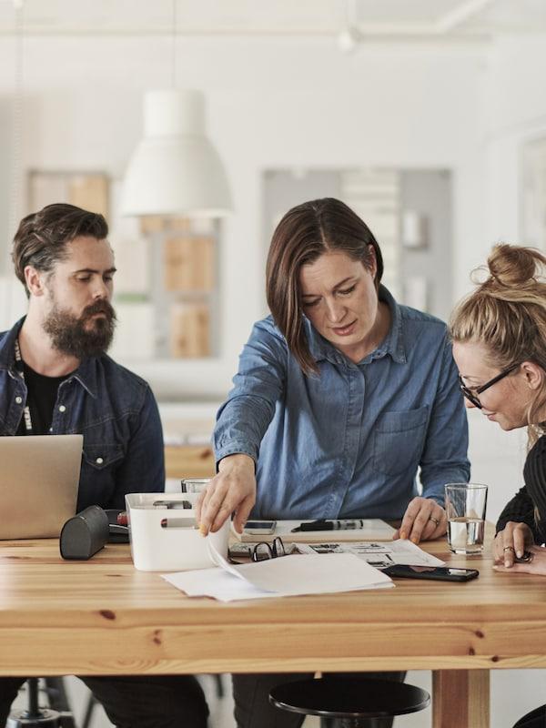 En IKEA-medarbeider med ei gul trøye prater med en kvinne mens hun tar notater med en penn.