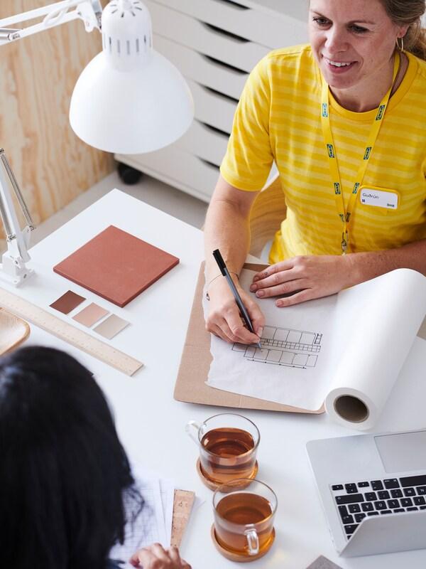 En IKEA-medarbeider med gul trøye prater med en kunde og tar notater på ei skisse på et skrivebord med ei hvit lampe.