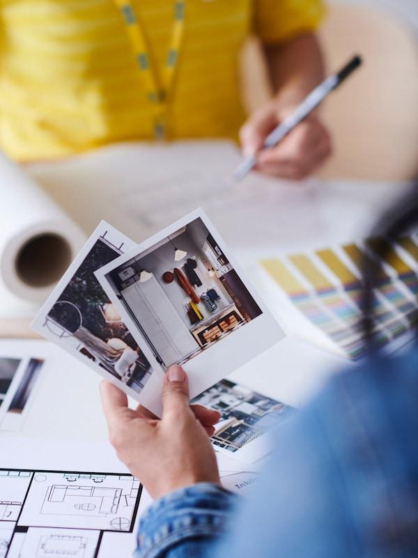 En IKEA medarbejder og en kunde sidder over for hinanden ved et bord. IKEA medarbejderen tager noter, mens kunden kigger på forskellige inspirationsbilleder.