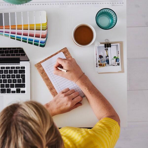 En IKEA medarbejder tager noter på et stykke papir på et skrivebord ved siden af en åben laptop. På bordet står der også en kop te og et glas vand, og der ligger forskellige farvepaletter og billeder til inspiration.