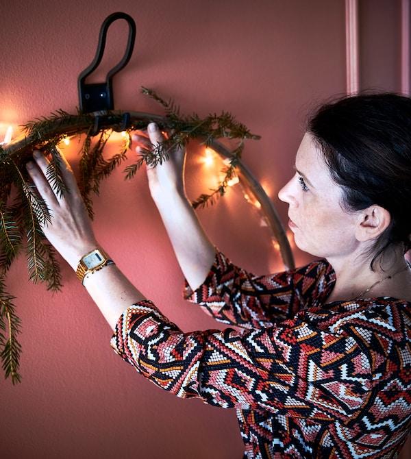 En interiørdesigner henger en dekorert hula-bøyle på veggen.