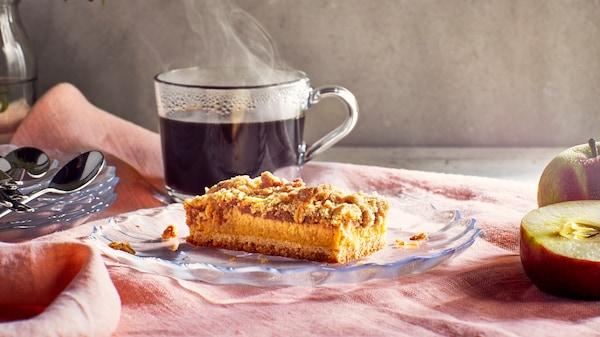 En KAFFEREP äppelkaka ligger på ett glasassiett och har en rykande het kopp kaffe bakom sig.