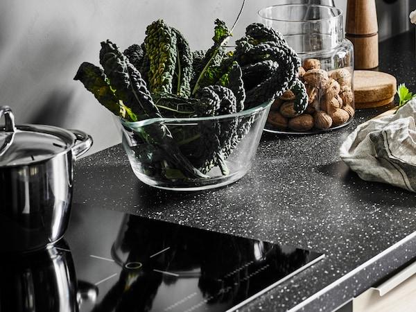 en köksbänk med SÄLJAN bänkskiva av laminat med svart mineralmönster.