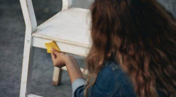 En kvinde, der slider en stol med sandpapir