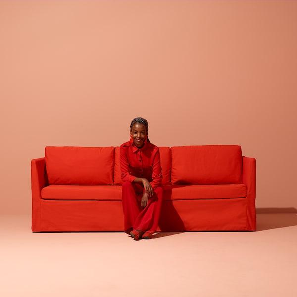 En kvinde i rødt tøj sidder i en rød sofa.