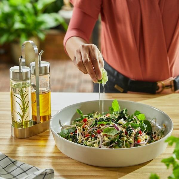 En kvinde klemmer saften fra en lime over en grøn salat i en salatskål. Ved siden af står et oliesæt.