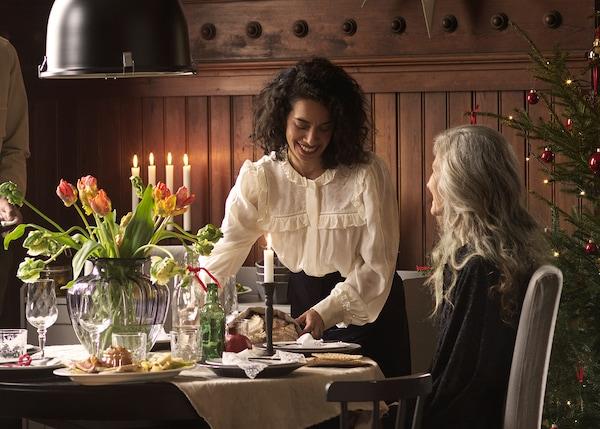 En kvinde serverer mad for en anden ved kvinde ved et festligt dækket bord. I baggrunden ses et juletræ.