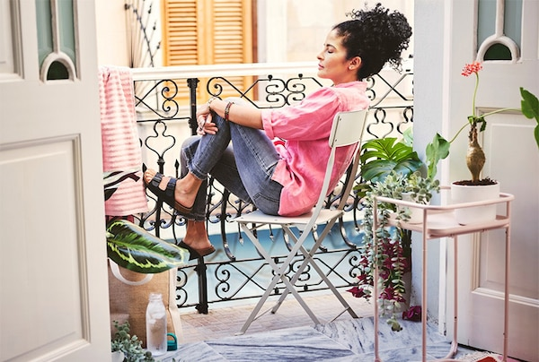 En kvinde sidder i en havestol og nyder solen på sin altan.