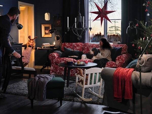 En kvinde sidder i en rød sofa med mønster med sin hund. Der hænger en stor julestjerne i baggrunden.