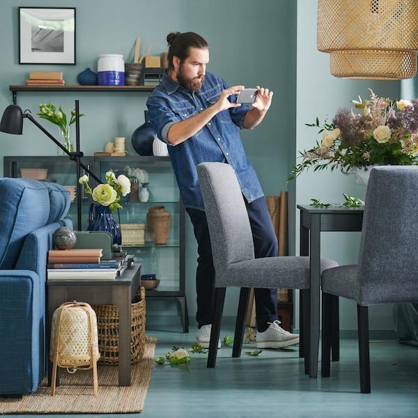 En kvinde sidder i grå, traditionel en sofa med hovedtelefoner og en tablet.