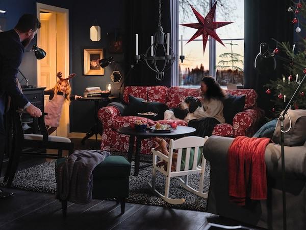 En kvinde sidder med sin hund i en rødblomstret sofa, mens hun kigger på sin datter, der titter ind gennem en døråbning.