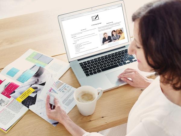 En kvinde sidder ved sin computer og planlægger sit nye køkken.