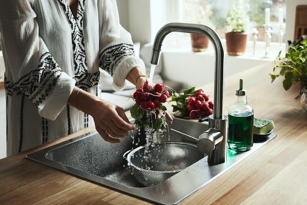 En kvinde skyllder radiser under en vandhane. Hun har en skål i vasken til at opsamle vand, som hun kan genbruge.