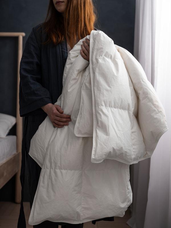 En kvinde står ved en seng i et soveværelse med dæmpet belysning, grå vægge og hvide, tynde gardiner. Hun holder en FJÄLLARNIKA dyne.