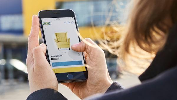 En kvinna handlar via sin mobil, i bakgrunden syns ingången till ett IKEA varuhus.
